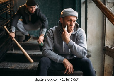 Two male hooligans are sitting on the stairs