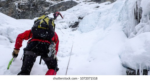 two male ice climbers on a frozen ice fall in deep powder snow in winter in the Alps of Switzerland