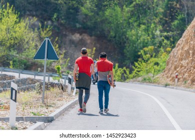 Two male longboarders carrying their longboards in their hands while climbing uphill and preparing for a downhill slide. Wearing red t-shirts, green hat, and super cool sunglasses.