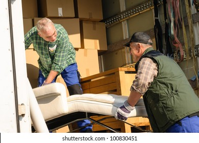 Two male movers putting furniture and boxes  in moving truck