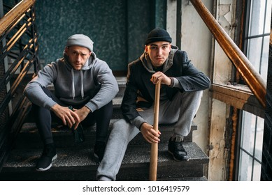 Two male robbers are sitting on the stairs