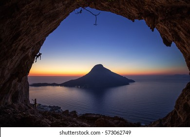 Two male rock climbers at sunset, Kalymnos Island, Greece. Climbing in cave against beautiful view of Telendos Island.