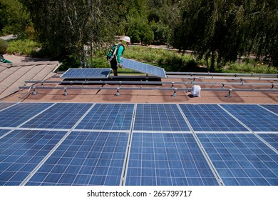 Two male solar workers install solar panels on home in Oak View, Southern California