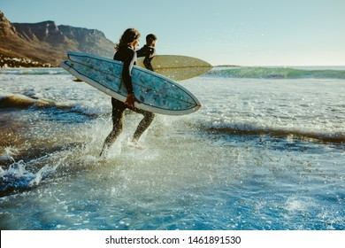 Two male surfers going for surfing in the sea. Two men carrying surfboards running in to the sea for surfing.