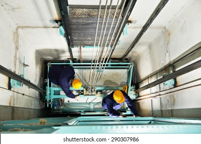 two male technician machinist worker at work adjusting elevator mechanism of lift with spanner