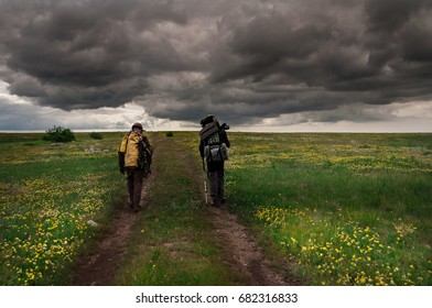 Two male tourists with backpacks walk along the mountain path