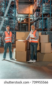 two male warehouse workers with digital tablet smiling at camera