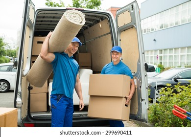 Two Male Workers Carrying Carpet And Cardboard Boxes In Front Of Van