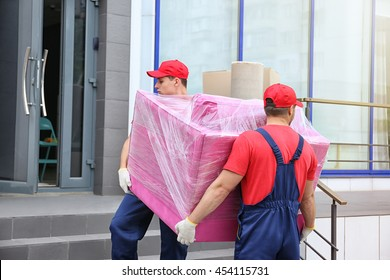 Two male workers with pink armchair