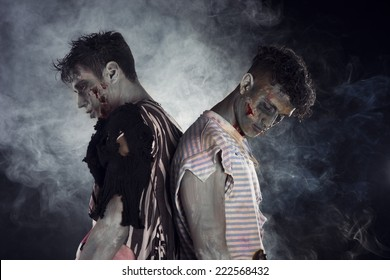 Two male zombies back to back on black smoky background, looking down and away