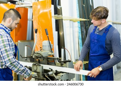 Two  males working on a machine in plant