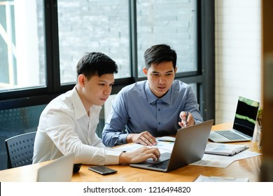 Two man business discussion with laptop computer and finance document paper.