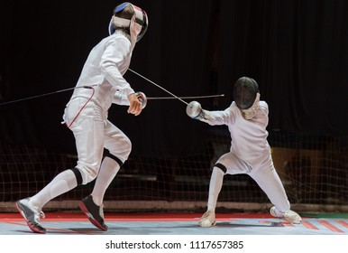 Two man fencing athletes fight on professional sports arena