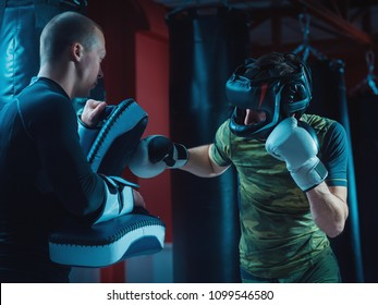 Two Man Fighters training together with punching pads at gym. Guy in protective doing kickboxing workout with her coach.