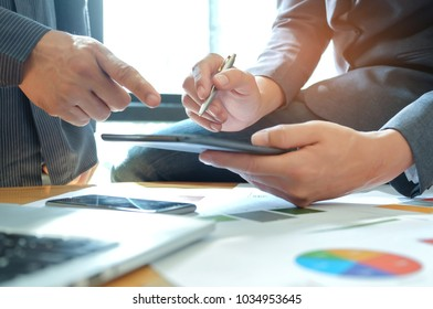 Two man hand are using a tablet,Team is working on data analysis with laptop and graph on the desk,lmage for business concepts.