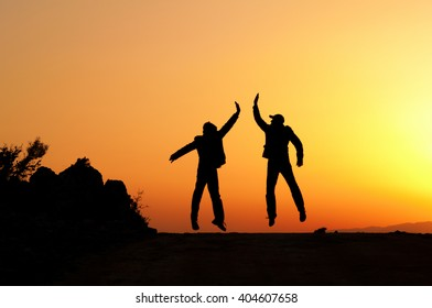 Two man holding for hands and jumping. They are successful people.