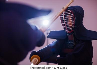 Two man kendoka fighting wooden sword. Japanese martial art of sword fighting.