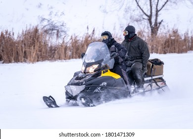 Two man on a snowmobile riding on the snow surface in the winter forest. Two men are riding a snowmobile quickly through the white snow.