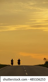 Two man riding motorcycle against sunset in the background.Silhouette of two man riding motorcycles towards the beautiful sky background. Summer vacation and travel concept