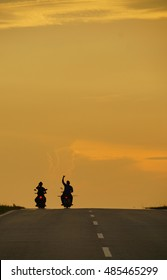 Two man riding motorcycle against sunset in the background.