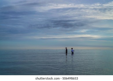 Two man is in the sea in the morning.