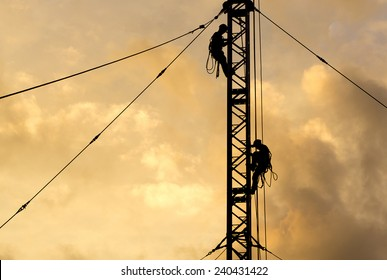 Two Man in silhouette working on communication or electricity tower