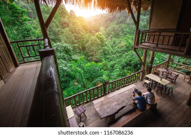 Two man sitting on tree house stairs in tropical forest