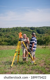 Two man survey crew working outdoors on a sunny day. They converse near an electronic distance meter and tripod.