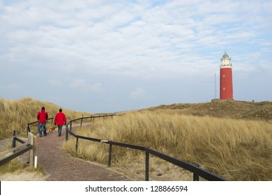 Two man are walking to red lighthouse