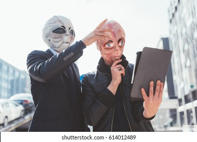 Two man wearing alien masks using tablet hand hold outdoor in city back light - strange, technology, halloween concept