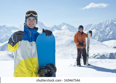Two man with winter sport equipment looking at camera. One is showing a blank lift pass. Concept to illustrate ski admission fee