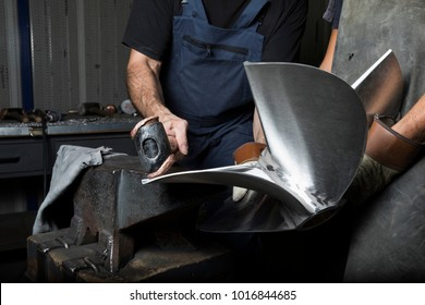 two man work with anvil and hammer on boat propeller
