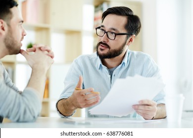 Two managers discussing financial documents at meeting