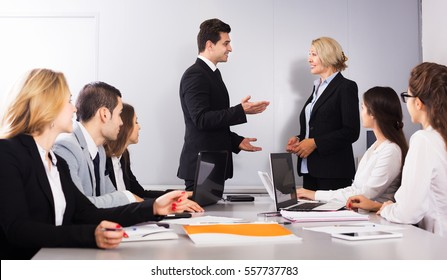 Two managers handshaking and celebrating advantageous deal in office interior. Focus on standing man