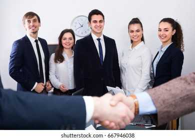 Two managers shaking hands at positive business meeting in office