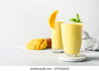 Two mango lassi in glasses on gray background with copy space. Indian healthy ayurvedic cold drink with mango. Freshness lassi made of yogurt, water, spices, fruits and ice.