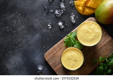 Two Mango lassi or smoothies on black background, top view with copy space. Indian traditional cold mango lassi made of yogurt, water, spices, fruits and ice.