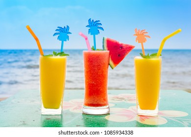 Two mango shake glasses and watermelon shake with decoration on the tropical beach