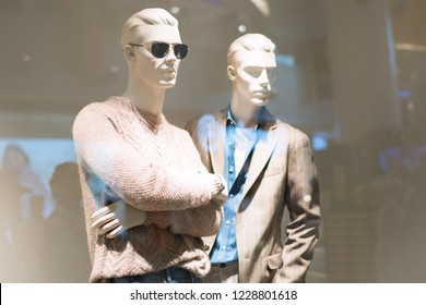 Two mannequins standing in store window display of women's casual clothing