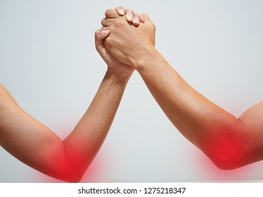 Two man's hands clasped arm wrestling (strong and weak), Unequal match,elbow pain,elbow inflammation in red point.healthcare concept.