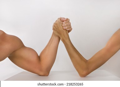 Two man's hands clasped arm wrestling (strong and weak), Unequal match