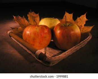 Two maple leaves and three apples in scuttle
