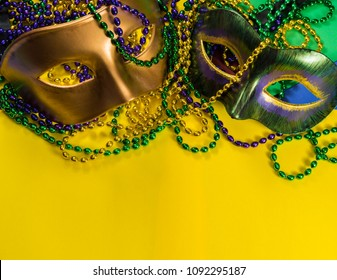Two Mardi Gras mask with colorful beads on a yellow background