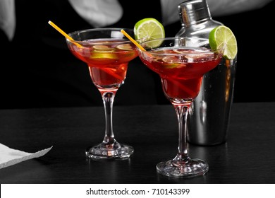 Two margarita glasses on a bar counter, a metal shiny shaker, a bartender on a dark blurred background.