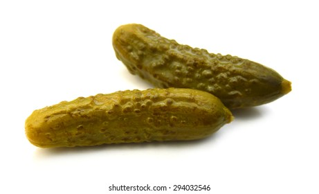 two marinated pickled cucumbers isolated on white