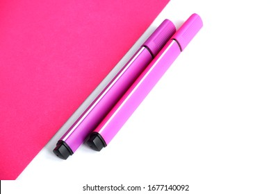 Two markers-pink and purple on a pink and white background. School supplies. Suitable for advertising background