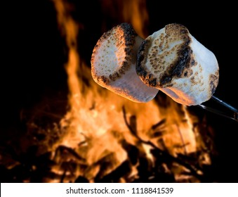 Two marshmallows being roasted over a campfire to make smores