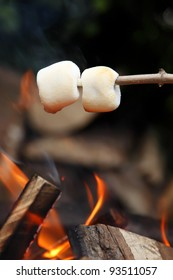 Two marshmallows roasting on the camp fire and getting nicely golden brown.