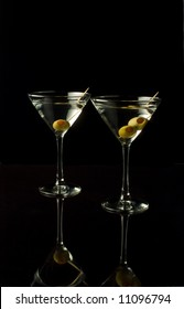 Two martinis isolated against black. with reflections