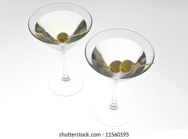 Two martinis with olives back lit on white.